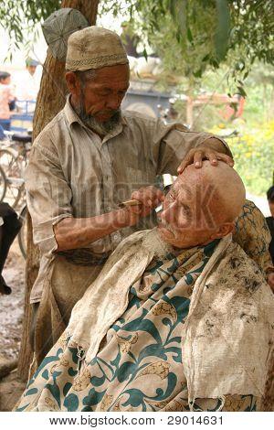 ein Weltweites Uigurisches Mann immer eine Rasur und Haarschnitt auf ein im freien Friseur in Kashgar, china