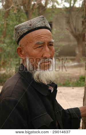 ein Weltweites Uigurisches Mann von Kashgar China auf der Suche über Vieh auf einer tierischen Auktion