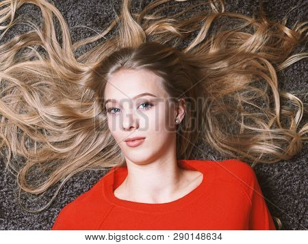 Young Woman Lying On Her Back With Long Blond Hair Spread Out