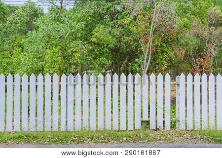 Old White Wooden Fence With A Broken Board At The Roadside Area