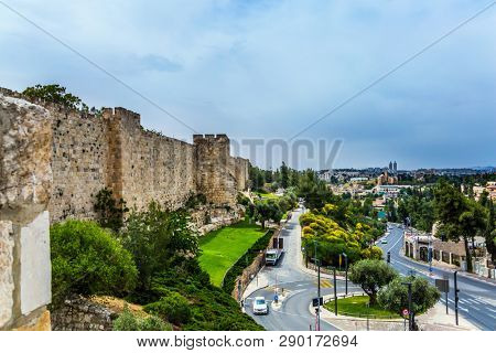 The light stone walls of Jerusalem sprouted in tufts of grass. Dizzy walk on the walls of Jerusalem. Eternal Jerusalem. The concept of historical and ethnographic tourism