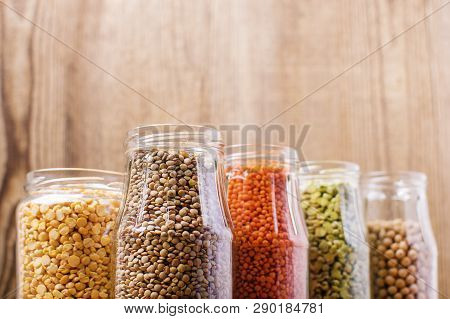 Different Legumes In Glass Jars Chickpeas, Green Peas, Red Lentils, Canadian Lentils, Black Lentils,