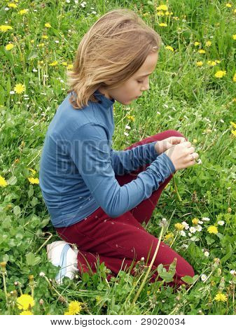 Young girl sitting on grass picking flowers
