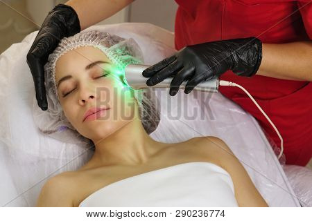 Hardware Cosmetology. Ultrasound Chromotherapy. Beautician Carries Out Procedure For Tightening Skin