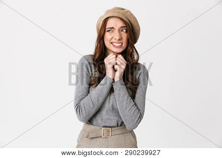 Portrait of humble woman 30s wearing hat frowning and looking guilty isolated over white background