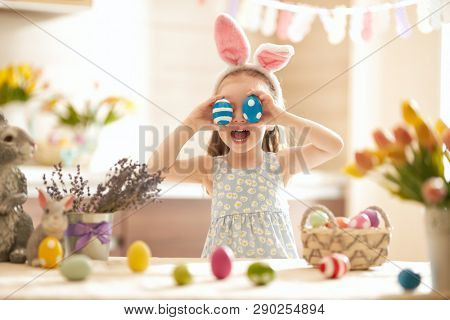 Beautiful child painting eggs. Happy family preparing for Easter. Cute little girl is wearing bunny ears.