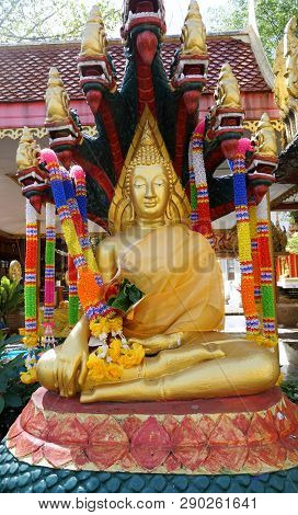 Buddha with the heads of Naga forming a protective taper around the Buddha head in temple at Thailand, Buddha Sheltered by Naga Hood, Vertical poster