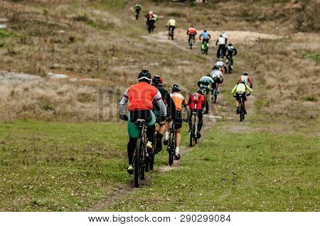 Group Of Male Cyclists Riding Uphill Following Each Other