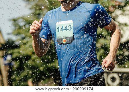 Male Runner Running Marathon In City In Foreground Splashing Water