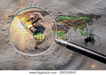 Collage With Magnifying Glass Searching At The Earth Map With Huge Hurricane, And Hurricane Eye Abov