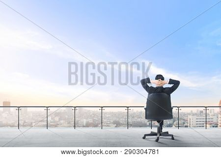 Rear View Of Asian Businessman Sitting On The Office Chair In Modern Terrace Relax And Looking At Vi