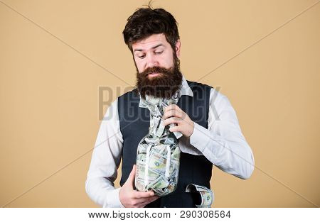 Personal accountant. Businessman with his dollar savings. Richness and wellbeing. Security and money savings. Banking concept. Man bearded guy hold jar full of cash savings. Safe place to keep money poster