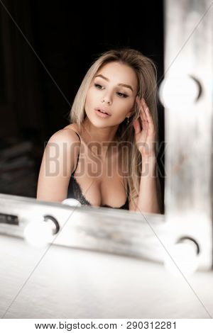 10bdfe0af70 Sexy young blond woman with a beautiful body with a magnificent breast in  an elegant lace bra sits in a dark room near a vintage mirror.