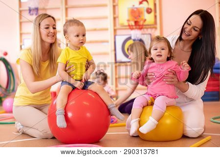 Mothers With Babies Doing Exercises With Gymnastic Ball In Gym. Concept Of Caring For The Childs Hea