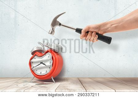 A Mans Hand Holding A Hammer And Crashing A Retro Alarm Clock Standing On The Wooden Floor.