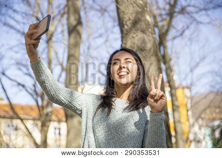 Carefree Woman Grimacing And Taking Selfie Photo Outdoors.  Smiling Pretty Young Lady Posing, Showin