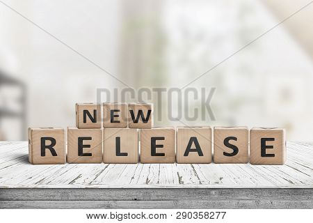 New Release Sign On A Wooden Table In A Bright Room With A Green Tone