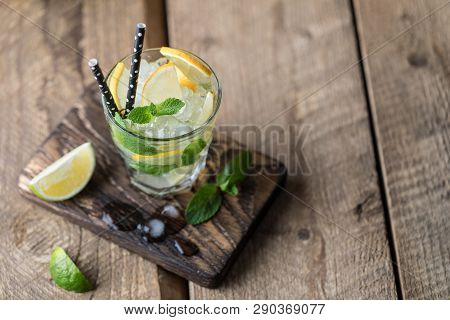Mojito Cocktail With Lime, Lemon And Mint In A Glass On A Dark Rustic Background. Fresh Summer Cockt