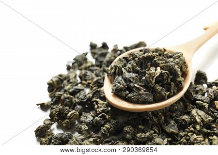 Tie Guan Yin Oolong Tea Leaves And Spoon On White Background, Closeup