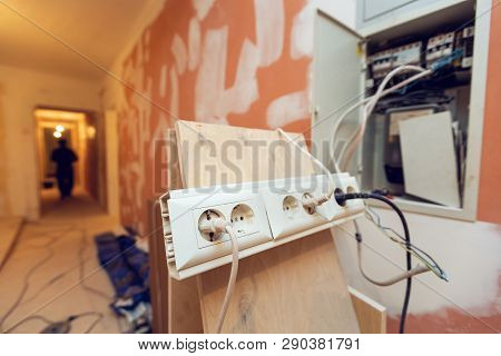 Temporary  electrical outlets for constructions tools and gears is connected up electrical box in apartment is inder construction, remodeling, renovation, overhaul, extension, restoration and reconstruction. Concept of home improvement. poster