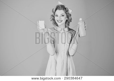 Cleanup, cleaning services, wife, gender. Pinup woman hold soup bottle, sponge. Housekeeper in uniform with clean spray, sponge. Retro woman cleaner on pink background. Cleaning, retro style, purity. poster