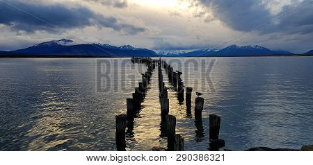 Lights Of The Sunset Over The Remains Of The Pier (muelle Braun Y Blanchard) In Puerto Natales, Chil