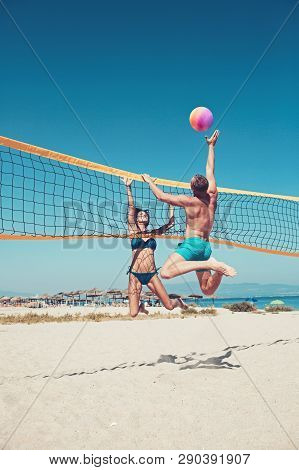 People Playing Beach Volleyball Having Fun In Sporty Active Lifestyle. Man Hitting Volley Ball In Ga