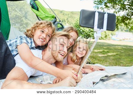 Family with two kids in tent is taking a selfie with smartphone on selfie stick