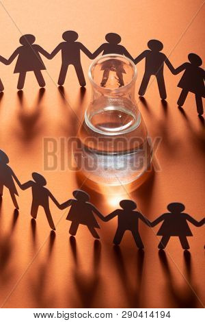 Circle of paper people holding hands in front of glass vial. Water scarcity global problem. Dependency, addiction concept.
