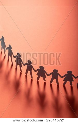 Paper people holding hands on red surface. Community, brotherhood concept. Society and support.
