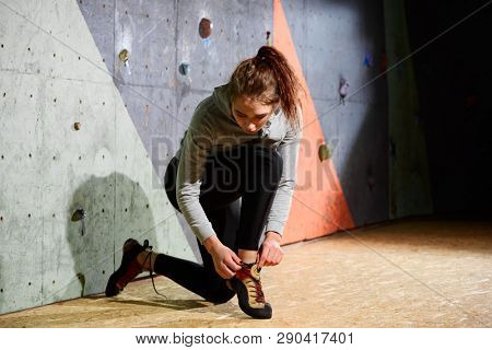 Young Active Woman Preparing for Bouldering on the Artificial Rock in Climbing Gym. Extreme Sport and Indoor Climbing Concept