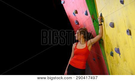 Young Active Woman Resting after Bouldering near the Colorful Artificial Rock in Climbing Gym. Wide Photo with Space for Text. Extreme Sport and Indoor Climbing Concept