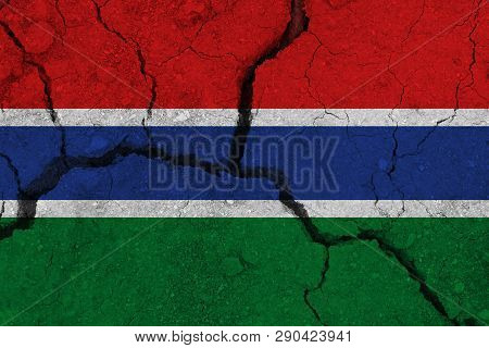 Gambia flag on the cracked earth. National flag of Gambia. Earthquake or drought concept poster