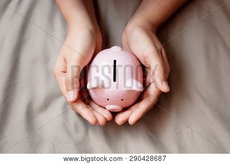 Close-up Hands Is Holding Piggy Bank On Fabric Background, Saving Money And Business Banking Or Fina