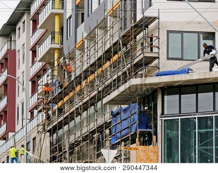 Gosford, New South Wales, Australia - March 18, 2019: Workmen Close Up, Dismantling Scaffolding And