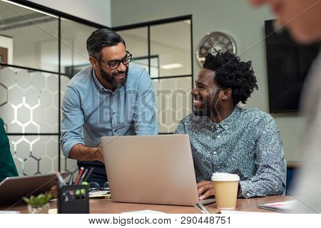 Two casual business partners sitting at table together and working. Group of smiling creative businesspeople working together. Mature businessman discussing affairs with african man in a meeting room.