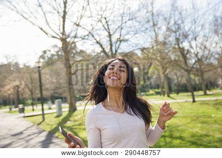 Excited Careless Girl Enjoying Favorite Music Outdoors. Beautiful Young Woman In Earphones Walking A