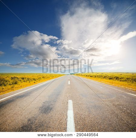 Driving on an empty asphalt road in the countryside with cloudy sky. Location place Ukraine, Europe. Active outdoor vacation. Scenic image of european travel destination. Discover the beauty of earth.
