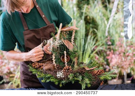 Commercial gardener creating a grave decoration for a funeral