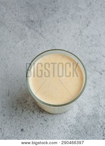 Healthy Drink Golden Turmeric Latte In Glass Cup. Yellow Homemade Latte On Gray Background. Detox Tu