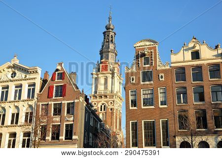 Crooked And Colorful Heritage Buildings, Located Along Kloveniersburgwal Canal, With Zuiderkerk Chur