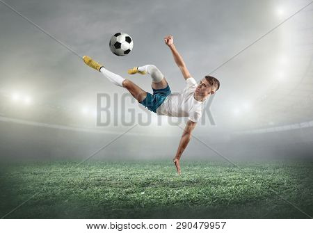 Soccer player on a football field in dynamic action at summer day under sky with clouds. Sporty man is shooting the ball outdoor. Sport, game concept.