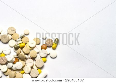 Pills of different sizes and colors and on a white isolated background. Concept of pharmaceutical industry, daily vitamins and minerals for women. Pregnancy, menopause poster