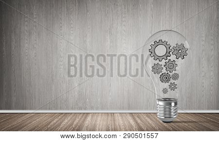 Glass Lightbulb With Multiple Gears Inside Placed In Empty Room With Grey Wall On Background. 3d Ren