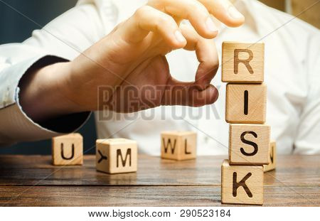 Hand Removes Blocks With The Word Risk. The Concept Of Reducing Possible Risks. Insurance, Stability