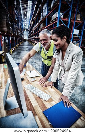 Side view of worker team is looking a computer and smiling in a warehouse