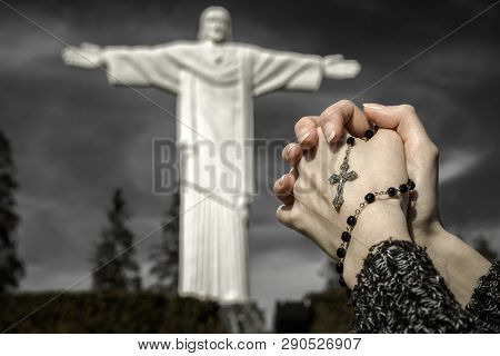 Praying Hands With Rosary And Statue Called Rio De Klin In Slovakia At Background