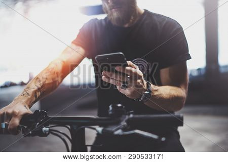 Tattooed Bearded Muscular Man In Holding Smartphone Hands And Using Maps App Before Riding By Electr
