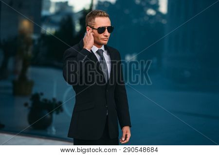 Male bodyguard uses security earpiece outdoors