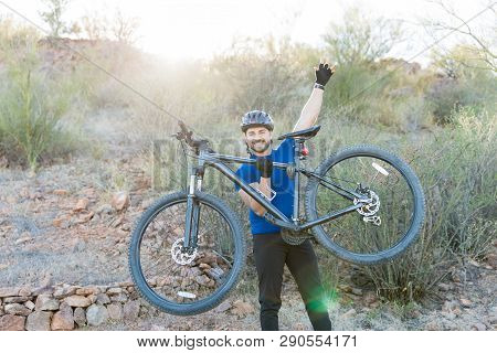 Fun Loving Man Raising Hand And Lifting Bicycle After Finishing Ride